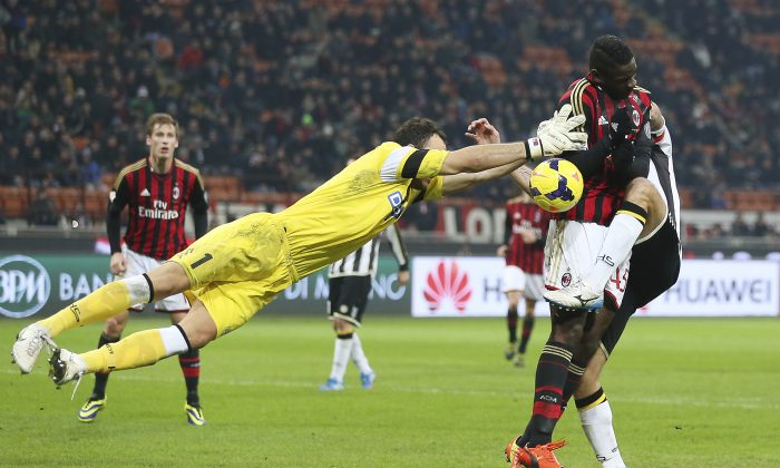 AC Milan forward Mario Balotelli, right, challenges for the ball with Udinese goalkeeper Zeljko Brkic, left, of Serbia, and Udinese defender Maurizio Domizzi during an Italian Cup soccer match at the San Siro stadium in Milan, Italy, Wednesday, Jan. 22, 2014. (AP Photo/Antonio Calanni)