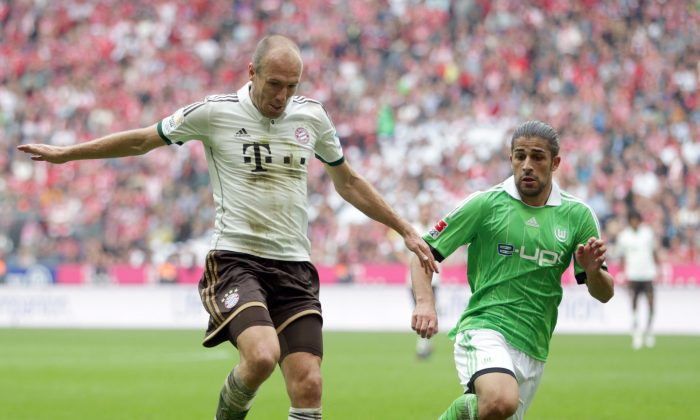 Wolfsburg's Ricardo Rodriguez of Switzerland, right, and Bayern's Arjen Robben of the Netherlands challenge for the ball during the German first division Bundesliga soccer match between FC Bayern Munich and VfL Wolfsburg, in Munich, southern Germany, Sat., Sept. 28, 2013. (AP Photo/Matthias Schrader)