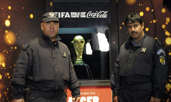 Algerian police officers guard the FIFA World Cup Trophy, Friday, Nov. 22, 2013, in Algiers. The trophy arrived Thursday for a two-day exhibition which will open to the public on Friday.  The soccer mad country Algeria qualified Tuesday for the 2014 World Cup Finals. (AP Photo/Sidali Djarboub)