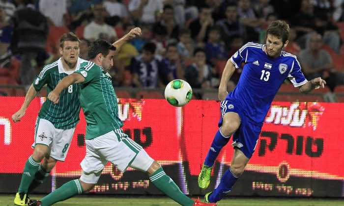 Northern Ireland's Martin Paterson, left and and Israel's Sheran Yeini fight for the ball during World Cup Group F qualifying soccer match in Ramat Gan stadium near Tel Aviv, Israel, Tuesday, Oct. 15, 2013. (AP Photo/Tsafrir Abayov)
