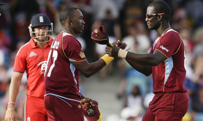 West Indies' Darren Sammy, right, and Dwayne Bravow shake hands after defeating England by 27 runs during their first T20 International cricket match at the Kensington Oval in Bridgetown, Barbados, Sunday, March 9, 2014. (AP Photo/Ricardo Mazalan)