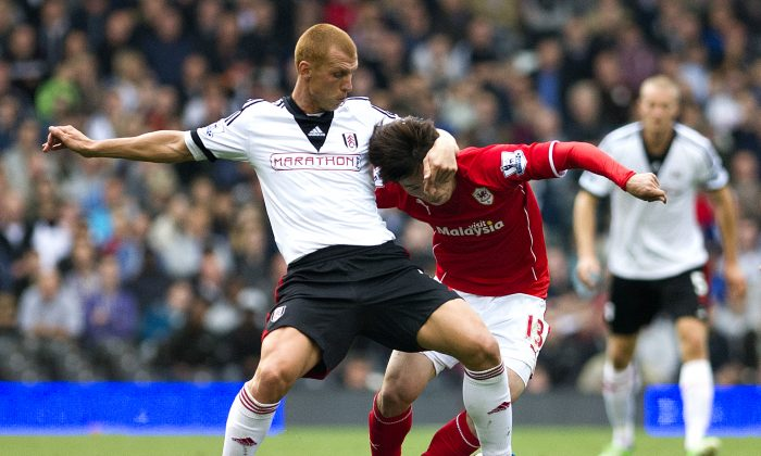 Fulham's Steve Sidwell, left, fights for the ball with Cardiff City's Kim Bo-Kyung during their English Premier League soccer match at the Craven Cottage stadium, in London, Saturday, Sept. 28, 2013. (AP Photo/Bogdan Maran)