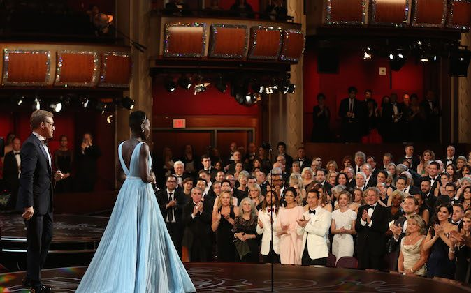 "Lupita Nyong'o receives a standing ovation as she accepts the award for best actress in a supporting role for ""12 Years a Slave"" during the Oscars at the Dolby Theatre on Sunday, Mar. 2, 2014, in Los Angeles. (Photo by Matt Sayles/Invision/AP)"