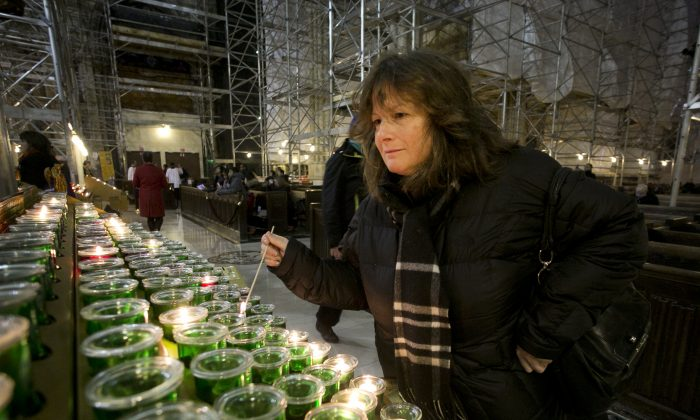 Katherine Miller lights a candle during Ash Wednesday service at St. Patrick's Cathedral, Wednesday, March 5, 2014 in New York. Some Protestant, and all Catholic churches, distribute ashes on the forehead as a sign of repentance and renewal on Ash Wednesday as the 40-day season leading to Easter begins. (AP Photo/Mark Lennihan)