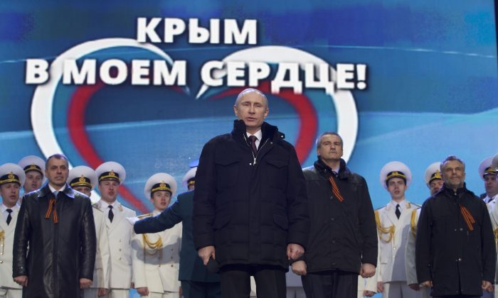 Russian President Vladimir Putin, with Crimean leaders in the background, sings the national anthem at a rally in support of Crimea joining Russia in Red Square in Moscow, Tuesday, March 18, 2014. (AP Photo/Pavel Golovkin)