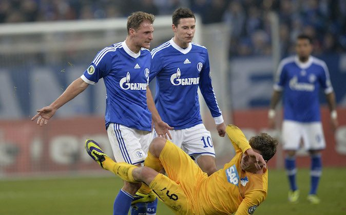 Schalke's Benedikt Hoewedes, left, clashes with Hoffenheim's Sven Schipplock, right, during the German soccer cup third round match between FC Schalke 04 and TSG Hoffenheim in Gelsenkirchen, Germany, Tuesday, Dec. 3, 2013. (AP Photo/Martin Meissner)
