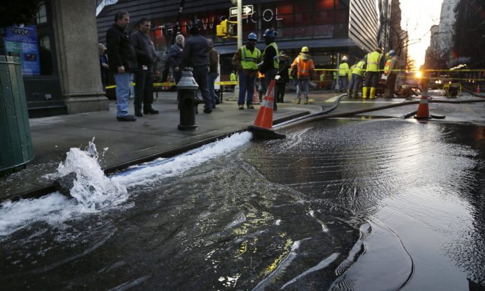 In this Jan. 15, 2014, photo water is pumped out of a hole in the middle of Fifth Avenue caused by a broken water main in New York. (AP Photo/Seth Wenig)