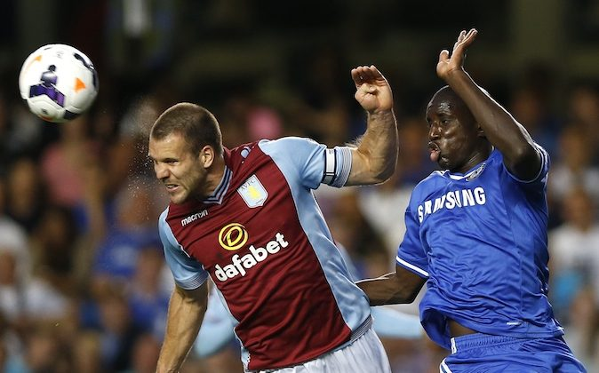 Chelsea's Demba Ba, right, vies for the ball with Aston Villa's Ron Vlaar during the English Premier League soccer match between Chelsea and Aston Villa at Stamford Bridge Stadium in London, Wednesday, Aug. 21, 2013. (AP Photo/Kirsty Wigglesworth)