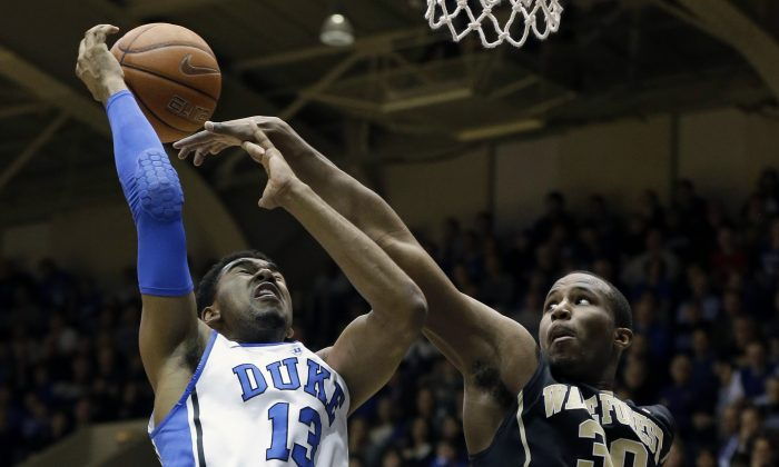 Duke's Matt Jones (13) is blocked by Wake Forest's Travis McKie (30) during the first half of an NCAA college basketball game in Durham, N.C., Tuesday, Feb. 4, 2014. (AP Photo/Gerry Broome)