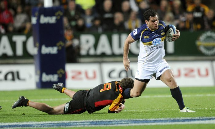 Brumbies' George Smith slips the tackle of Chiefs' Tawera Kerr-Barlow in the Super Rugby Final match at Waikato Stadium, Hamilton, New Zealand, Saturday, August 03, 2013.(AP Photo/SNPA, Ross Setford)
