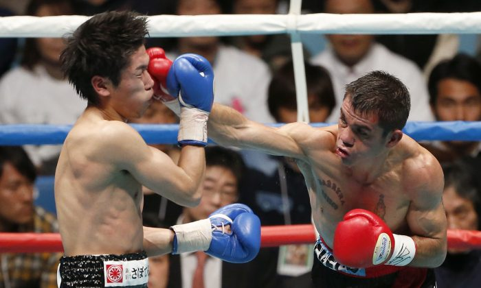 Argentine champion Juan Carlos Reveco, right, hits Japanese challenger Masayuki Kuroda during their WBA flyweight title match in Kawasaki, Japan on Feb. 27, 2013. Reveco defended his title by a unanimous decision. (AP Photo/Shizuo Kambayashi)