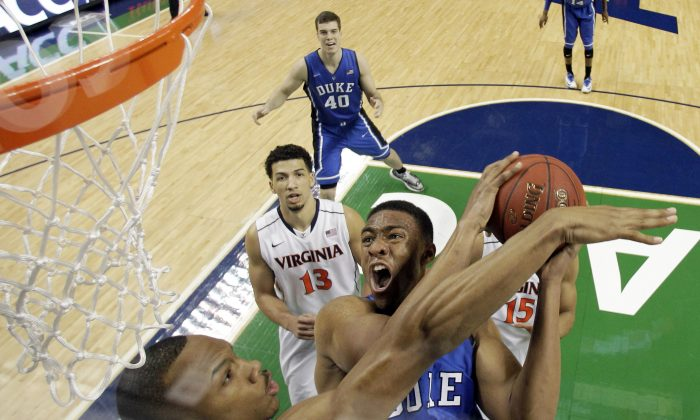 Duke's Jabari Parker (1) tries to shoot over Virginia's Darion Atkins during the first half of an NCAA college basketball game in the championship of the Atlantic Coast Conference tournament on Sunday, March 16, ahead of the selections for the NCAA tournament on Sunday night. (AP Photo/Bob Leverone)