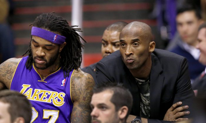 Injured Los Angeles Lakers player Kobe Bryant, right, sits on the end of the team bench next to Jordan Hill, left, during the first half of an NBA basketball game against the Phoenix Suns on Wednesday, Jan. 15, 2014, in Phoenix. (AP Photo/Ross D. Franklin)