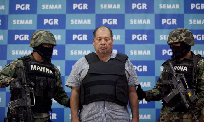 "Arrested drug boss Mario Cardenas Guillen, also known as ""El Gordo,"" is escorted by Mexican Navy officers in Mexico City, Sept. 4, 2012. Ingredients for methamphetamine, from China, help the Mexican drug trade. (AP Photo/Alexandre Meneghini)"