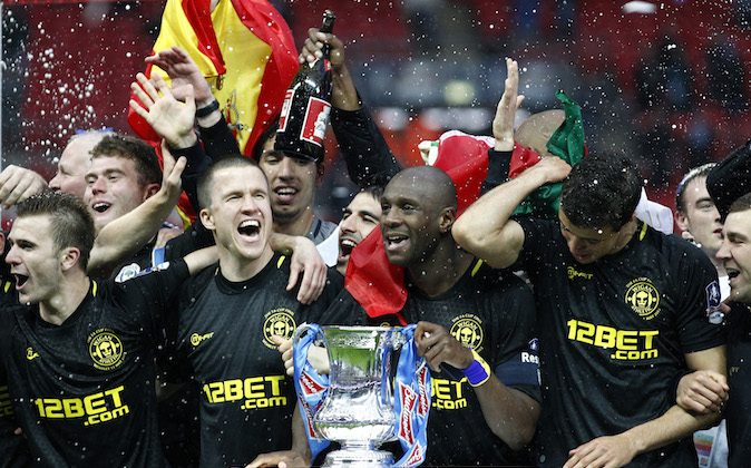 In this picture made available May 12 Wigan Athletic players including their captain Emmerson Boyce, centre right, celebrate after their 1-0 win over Manchester City in their English FA Cup final soccer match at Wembley Stadium, London, Sunday, May 12, 2013. (AP Photo/Jon Super)