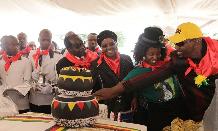 President Robert Mugabe, left, his wife Grace, daughter Bona and  her fiance Sam Chikoore cut his birthday cake  during celebrations to mark his 90th Birthday in Marondera about 100 kilometres east of  Harare, Sunday, February, 23, 2014.Mugabe who is Africas oldest leader has been  in power in the Southern African nation since 1980. (AP Photo/Tsvangirayi Mukwazhi)