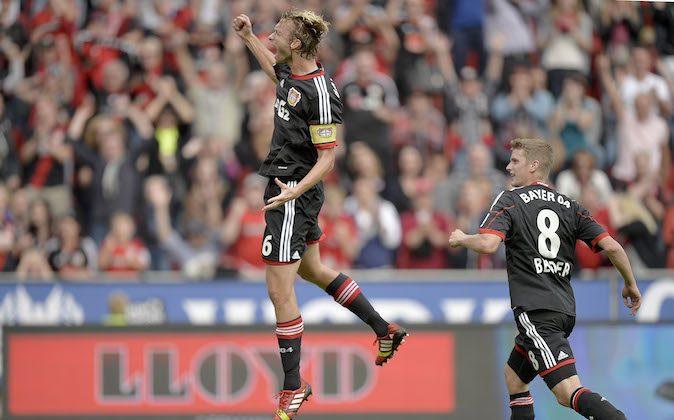 Leverkusen's Simon Rolfes, left, celebrates after scoring during the German soccer Bundesliga match between Bayer Leverkusen and Hanover 96 in Leverkusen, Germany, Saturday, Sept. 28, 2013. (AP Photo/Martin Meissner)