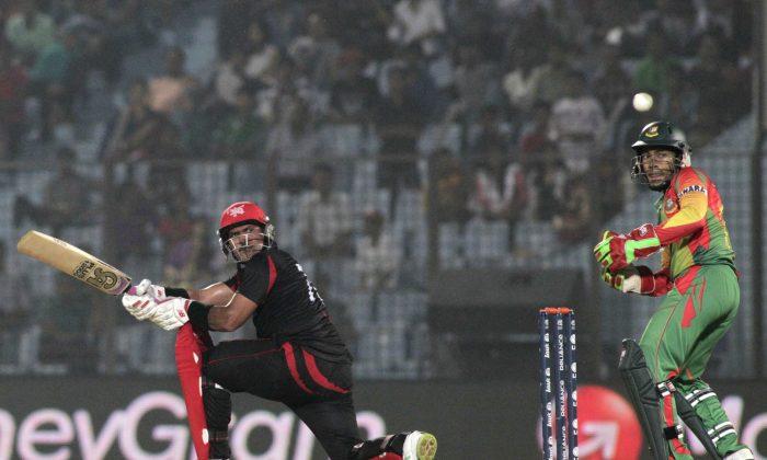 Hong Kong's Munir Dar, left, plays a shot as Bangladesh's captain Mushfiqur Rahim watches during their ICC Twenty20 Cricket World Cup match in Chittagong, Bangladesh, Thursday, March 20, 2014 . (AP Photo/Bikas Das)