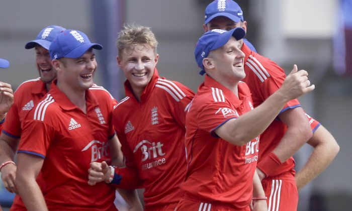 England's James Tredwell, right, celebrates with teammates after he caught Kirk Edwards during their second one-day international cricket match at the Sir Vivian Richards Cricket Ground in St. John's, Antigua, Sunday, March 2, 2014. (AP Photo/Ricardo Mazalan)