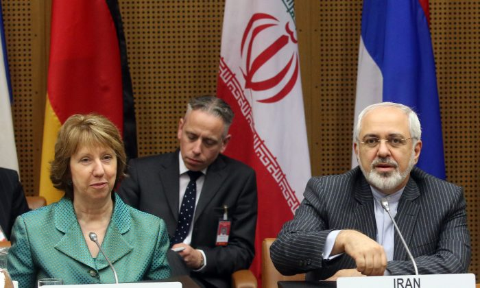European Union High Representative Catherine Ashton, left, and Iranian Foreign Minister Mohammad Javad Zarif, right, wait for the start of closed-door nuclear talks in Vienna, Austria, Tuesday, March 18, 2014. (AP Photo/Ronald Zak)