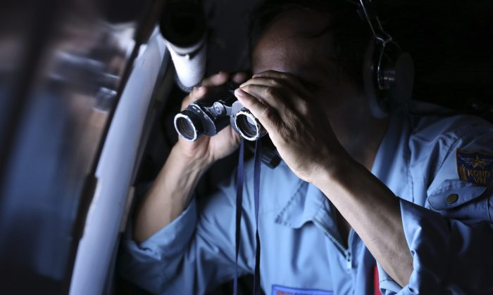 Vietnamese Air Force Col. Pham Minh Tuan uses binoculars on board a flying aircraft during a mission to search for the missing Malaysia Airlines flight MH370 in the Gulf of Thailand, Thursday, March 13, 2014. With no distress call, no sign of wreckage and very few answers, the disappearance of the Malaysia Airlines plane is turning into one of the biggest aviation mysteries since Amelia Earhart vanished over the Pacific Ocean in 1937. (AP Photo)