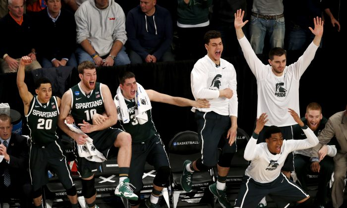 Michigan State players react during second half in a regional semifinal against Virginia at the NCAA men's college basketball tournament, early Saturday, March 29, 2014, in New York. (AP Photo/Julio Cortez)