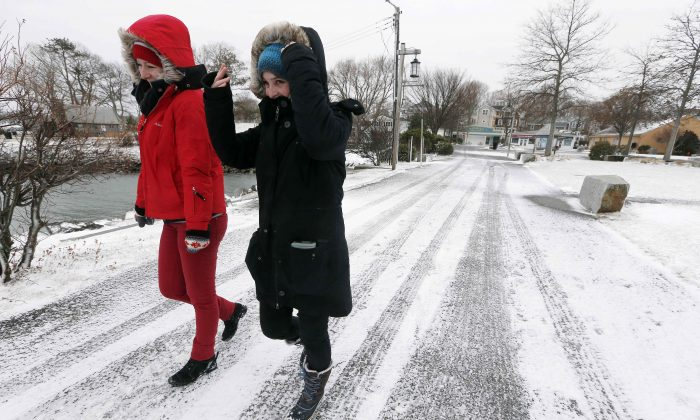 Jule Kuppinger, right, and Marie-Lena Marstaller, both of Germany, walk against the wind on their way to visit the Mayflower II  in Plymouth, Mass., Wednesday, March 26, 2014.  A spring storm brought high winds that whipped snow across portions of Massachusetts and eastern Maine on Wednesday. (AP Photo/Michael Dwyer)
