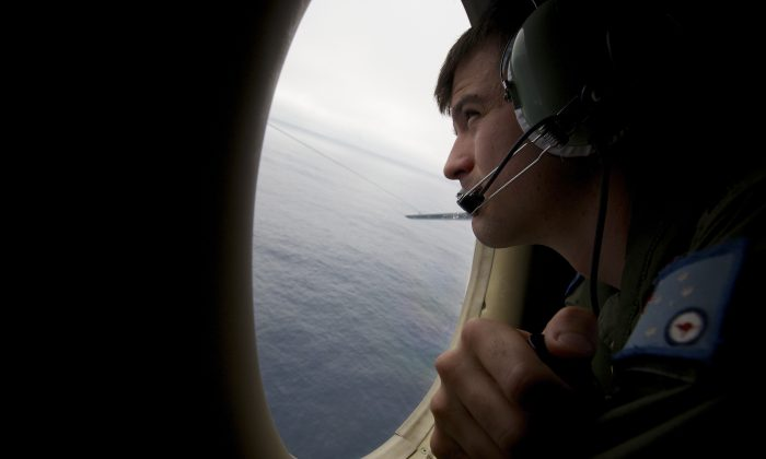 A crewman of an RAAF AP-3C Orion aircraft looking out his observation window whilst searching for missing Malaysia Airways Flight MH370, Monday, March 24, 2014. The search is being conducted in an area 2,500km off the South West coast of Perth after the Malaysian Airways aircraft went missing on 8th March 2014 whilst on a flight between Kuala Lumpur and Beijing.(AP Photo/Richard Wainwright/Pool)