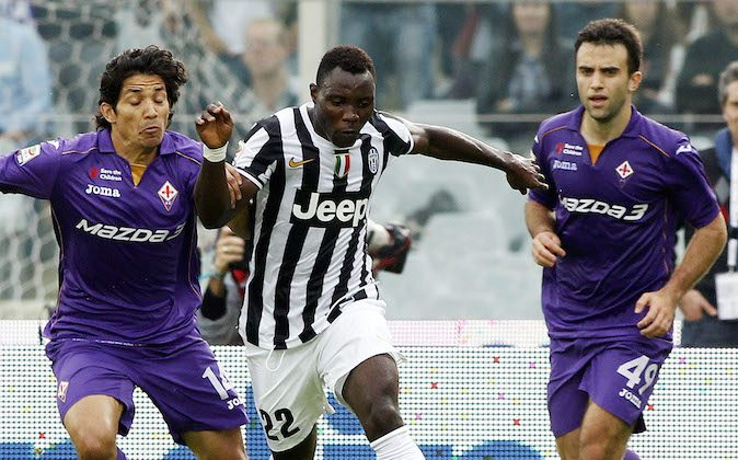 Juventus' Kwadwo Asamoah, of Ghana, center, controls the ball from Fiorentina's Mati Fernandez, of Chile, left, during a Serie A soccer match between Fiorentina and Juventus at the Artemio Franchi stadium in Florence, Italy, Sun., Oct. 20, 2013.  (AP Photo/Fabrizio Giovannozzi)