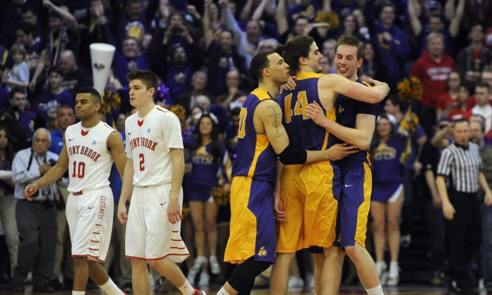 Albany's Gary Johnson (20), Sam Rowley (14), and Luke Devlin (11) celebrate as Stony Brook's Carson Puriefoy (10) and Kameron Mitchell (2) walk off the court after Albany beat Stony Brook 69-69 to win the championship of the America East Conference tournament NCAA college basketball game Saturday, March 15, 2014, in Stony Brook, N.Y. (AP Photo/Kathy Kmonicek)