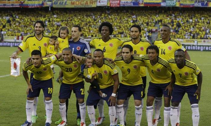 In this June 11, 2013 file photo, Colombia soccer national team pose prior to a 2014 World Cup qualifying match against Peru in Barranquilla, Colombia. Background from left: Mario Yepes, David Ospina, Carlos Sanchez, Abel Aguilar and Luis Perea. Foreground from left: Teofilo Gutierrez, Macnelly Torres, Camilo Zuniga, Radamel Falcao Garcia, Juan Cuadrado and Pablo Armero. The draw for the 2014 World Cup finals takes place Friday Dec. 6, 2013 near Salvador, Brazil. The 32 teams will be drawn into eight groups of four. The top two in each group will progress to the knockout stages. Twelve stadiums in twelve cities will host matches. (AP Photo/Ricardo Mazalan, File)