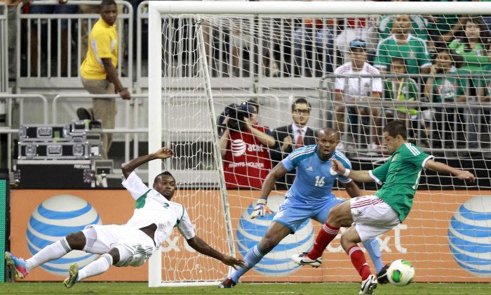 Mexico forward Javier Hernandez, right, attempts to shoot past Nigeria goalkeeper Austin Ejide (16) and defender Godfrey Oboabona (2) during the first half of a soccer game on Friday, May 31, 2013, in Houston. (AP Photo/Patric Schneider)