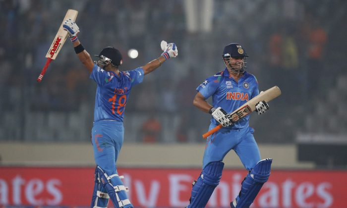 India's batsmen Suresh Raina, right, and Virat Kohli celebrate their victory over Pakistan in the ICC Twenty20 Cricket World Cup match in Dhaka, Bangladesh, Friday, March 21, 2014. (AP Photo/Aijaz Rahi)