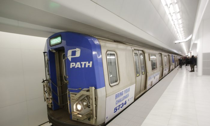 A commuter train leaves a newly-opened platform at the World Trade Center's PATH station, Tuesday, Feb. 25, 2014, in New York. The new platform will link towns in New Jersey with the World Trade Center's transportation hub, still under construction. The fully modernized platform A features new lighting, speakers, illuminated signs, escalators and elevators. (AP Photo/Mark Lennihan)