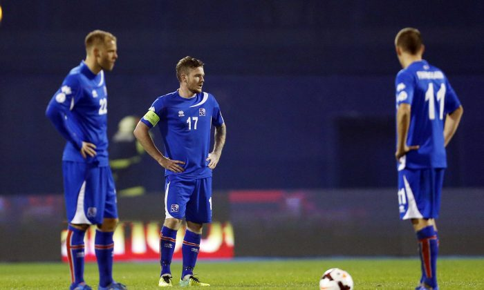 Iceland's Eidur Smari Gudjohnsen, left, Aron Gunnarsson, center and Alfred Finnbogason stand on the pitch after Croatia's second goal during their World Cup qualifying playoff second leg soccer match in Zagreb, Croatia, Tuesday, Nov. 19, 2013. (AP Photo/Darko Bandic)