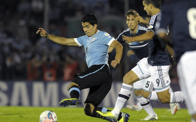 Uruguay's Luis Suarez, left center, fights for the ball with Argentina's Erik Lamela, right, as Lucas Biglia follows, during a 2014 World Cup qualifying soccer game in Montevideo, Uruguay, Tuesday, Oct. 15, 2013. (AP Photo/Matilde Campodonico)