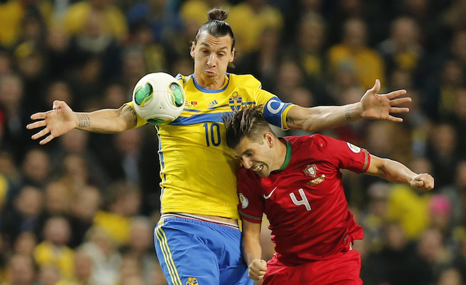 Sweden's Zlatan Ibrahimovic, left, and Portugal's Miguel Veloso challenge for the ball during the World Cup qualifying playoff second leg soccer match between Sweden and Portugal in Stockholm, Sweden, Tuesday, Nov.19, 2013. (AP Photo/Frank Augstein)