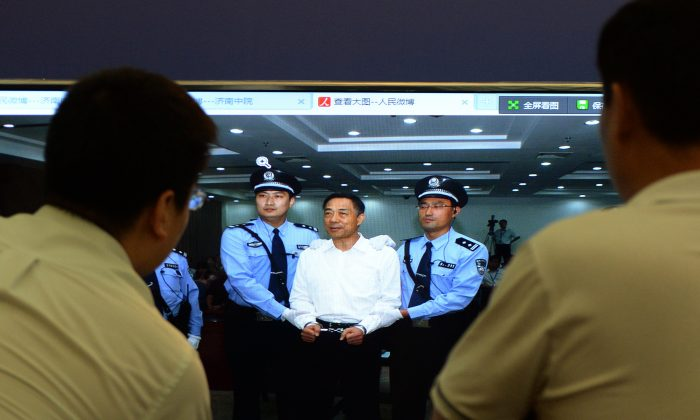 Staff look at an image of disgraced politician Bo Xilai at the Intermediate People's Court after being sentenced to life in prison when his verdict was announced in Jinan, Shandong Province on September 22, 2013.  Fallen Chinese political star Bo Xilai was sentenced by a court to life in prison, following a sensational scandal that culminated in the country's highest-profile trial in decades.               AFP PHOTO/Mark RALSTON        (Photo credit should read MARK RALSTON/AFP/Getty Images)