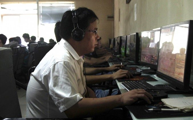 A Chinese man uses a computer at an Internet cafe in Beijing in 2010. Spies tied to some of China's largest cyberespionage campaigns are using the disappearance of Malaysian Flight MH 370 to infect computers of governments and think tanks. (AP Photo/Ng Han Guan)