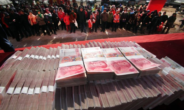 Villagers gather to receive their share of 1 million yuan (U.S. $165,000) paid out in year-end bonuses by a tea company at their village in the suburb of Jinan, east China's Shandong Province, Jan. 20, 2014. (STR/AFP/Getty Images)