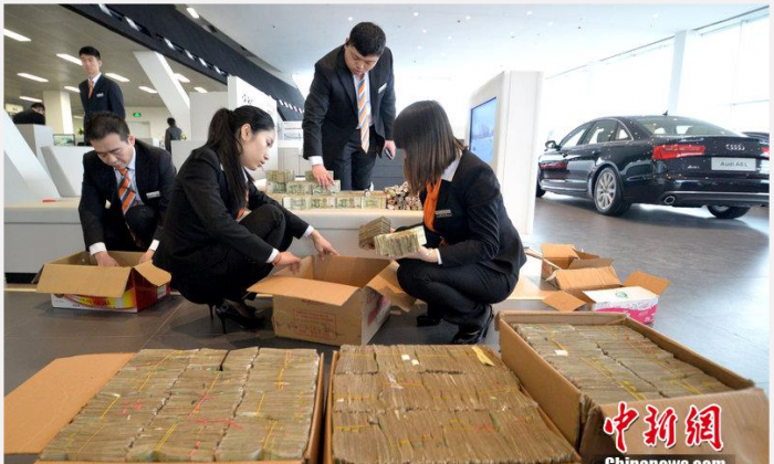 Bank tellers counting piles of money at a dealership in Hubei Province, after a customer bought in boxloads of 1 yuan notes and coins that he had been collecting for years. (Screenshot/China News)