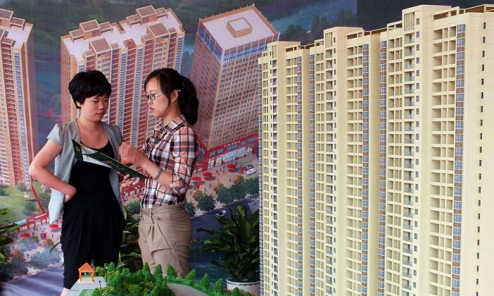 A Chinese home buyer makes inquiries about a new apartment project on display at a real estate fair in Yichang, central China's Hubei province on May 18, 2012. (AFP/AFP/GettyImages)