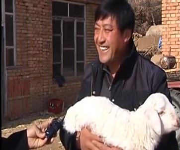 Sheep farmer Wang Jingfeng from Chifeng holding a lamb with seven legs. (Screenshot/YouTube)