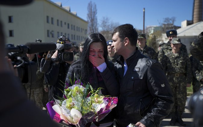 Two Lieutenants, Galina Volosyanchik, center left, and Ivan Benera, center right, react as they are welcomed by senior officers and comrades celebrating their wedding at the Belbek airbase outside Sevastopol, Crimea, on Saturday, March 22, 2014. Two young Lieutenants got married today and arrived to their unit for a short celebration as Russian troops continue to occupy part of the airbase and demand the surrender of Ukrainian airmen. (AP Photo/Ivan Sekretarev)