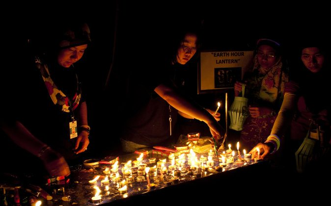 Women light candles as the lights go out in Kuala Lumpur, Malaysia, to celebrate Earth Hour in 2011. Earth Hour 2014 will be on Saturday, March 29 from 8:30-9:30 p.m. local time. (Shutterstock*)