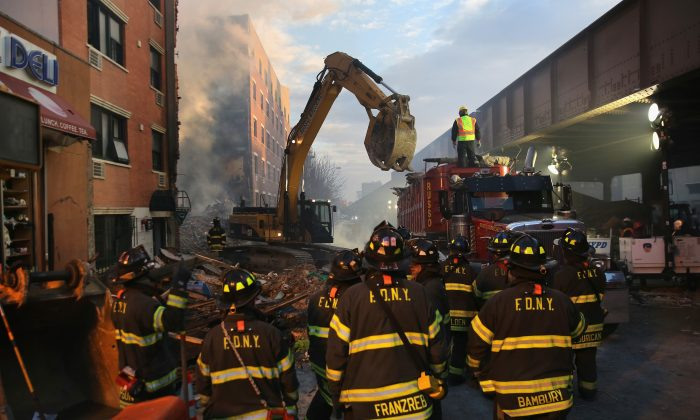 Firemen watch as work crews remove debris from the site of an explosion in East Harlem Thursday, March 12, 2014. (John Moore/Getty Images)