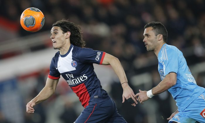 Marseille's Jeremy Morel of France, right,  challenges for the ball Paris Saint Germain's Edinson Cavani of Uruguay with during their French League One soccer match, at the Parc des Princes stadium, in Paris, Sunday, Mar. 2 , 2014. (AP Photo/Lionel Cironneau)