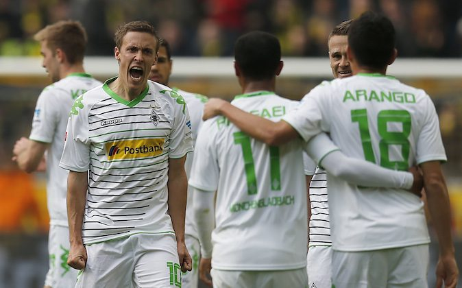 Moenchengladbach's Max Kruse, second from left, celebrates with teammates after scoring  during the German first division Bundesliga soccer match between BvB Borussia Dortmund  and VfL Borussia Moenchengladbach in Dortmund, Germany, Saturday, March 15, 2014. (AP Photo/Frank Augstein)