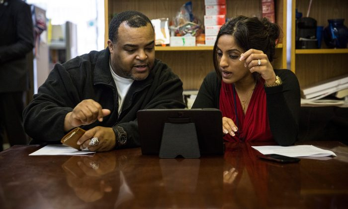 Arthur Barrett (L) works with Sherin Jose of the Bronx Community Health Network to sign up for the Affordable Care Act in the Bronx, New York, on March 31, 2014. (Andrew Burton/Getty Images)