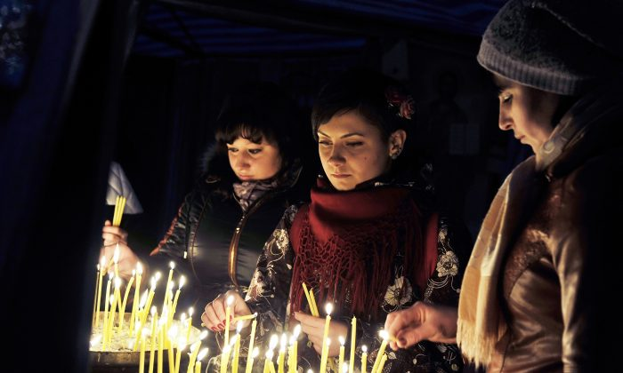 Young women light candles at a makeshift shrine in Kyiv's Independence square as protests continued nearby on March 2, 2014. (Louisa Gouliamaki/AFP/Getty Images)